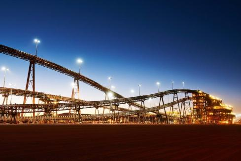 BHP raises iron ore forecast, flags coal hit